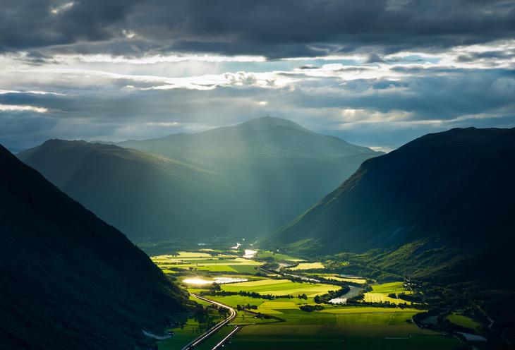 Fjell, skyer og grønne jorder i Sel kommune