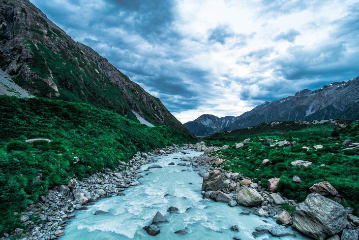 Elv renner gjennom grønn dalbunn med høye fjell og skyer på himmelen.