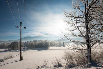 Vinterdag med elektriske linjer, sol og fjell i bakgrunnen