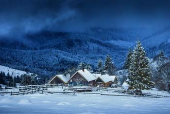Julepyntet hus med snø, om kvelden i fjellet