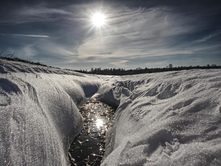 Vinter og sol med smeltende hull i snøen