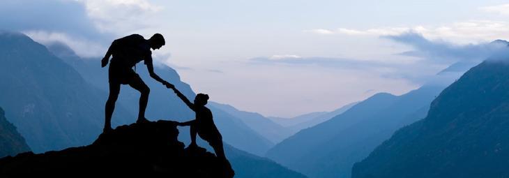 En hjelpende hånd til fjelltoppen i solnedgang.