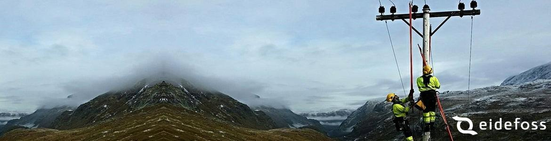 To av Eidefoss Nett sine montører høyt i en mast på fjellet.