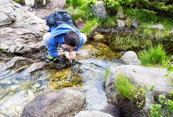 Ung mann som drikker vann fra en bekk i vårlige omgivelser.