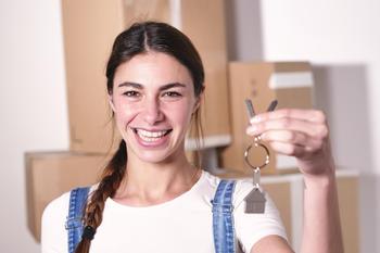 Ung dame som holder frem nøkkelen til sitt nye hjem.