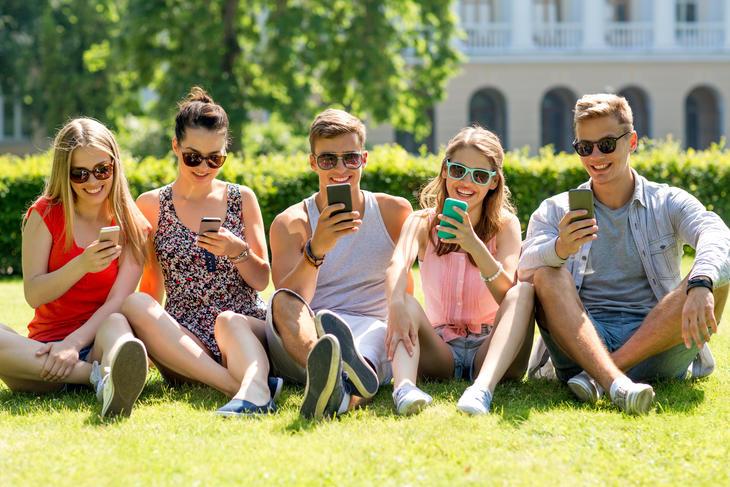 Studenter i parken  med mobiltelefon.