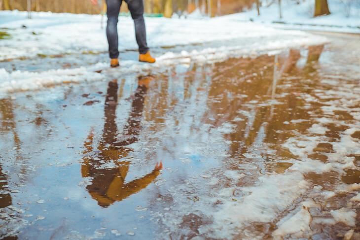 Smeltet snø i veien, som en person prøver å krysse.