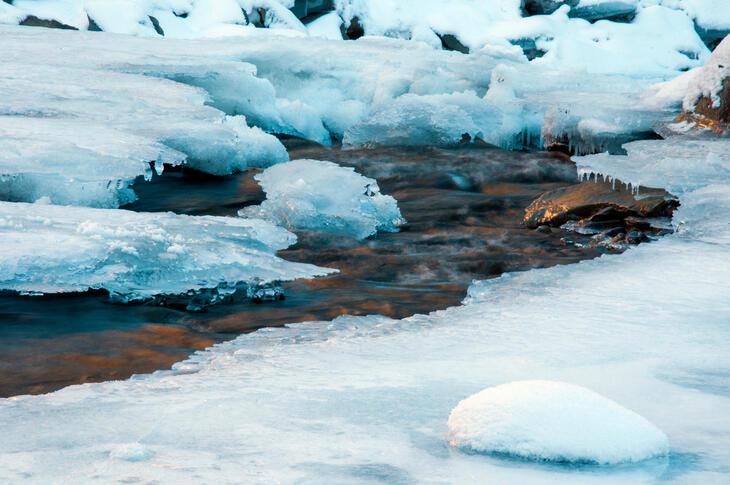 Elv som renner under is om vinteren.